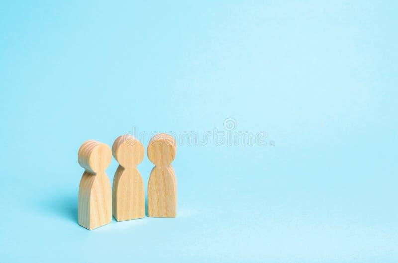 Três povos estão junto e discutem em um fundo azul Uma comunicação e discussão entre três amigos foto de stock