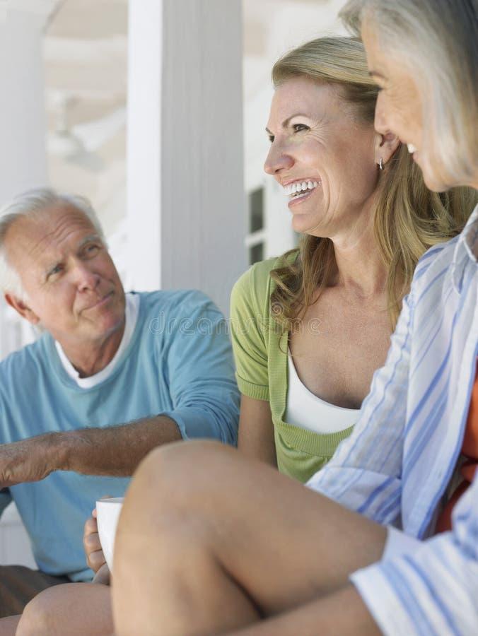 Três povos maduros que sentam-se na varanda foto de stock royalty free