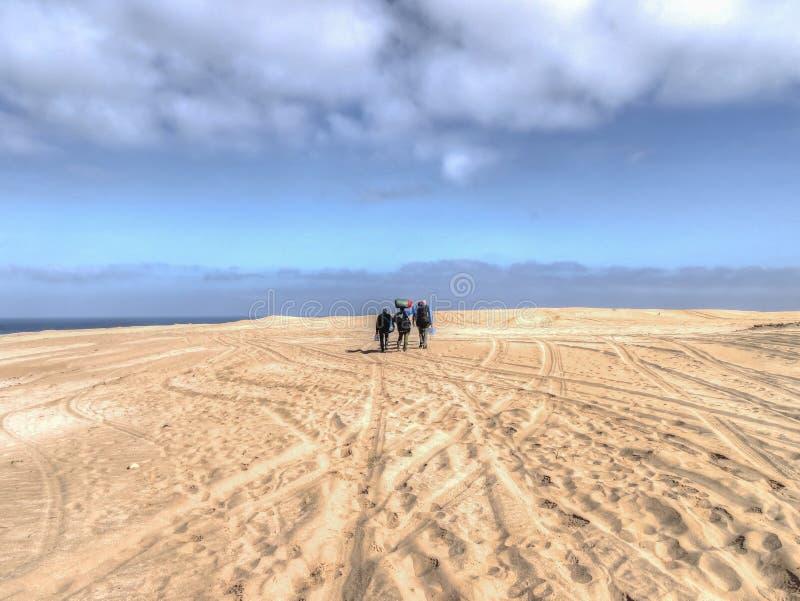 Três povos que andam através do terreno arenoso fotografia de stock royalty free