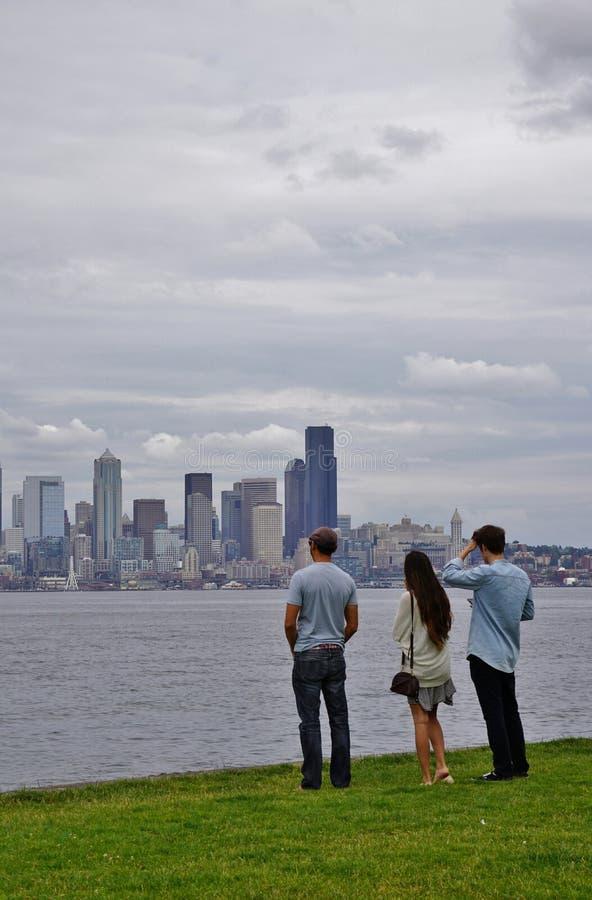 Três povos que olham a skyline de Seattle de Alki Beach em Seattle ocidental fotos de stock