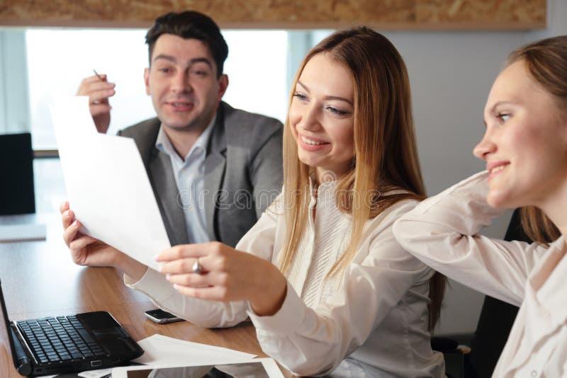 Três povos que trabalham no escritório com originais fotografia de stock royalty free