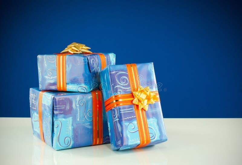 Três presentes de Natal de encontro ao fundo azul foto de stock