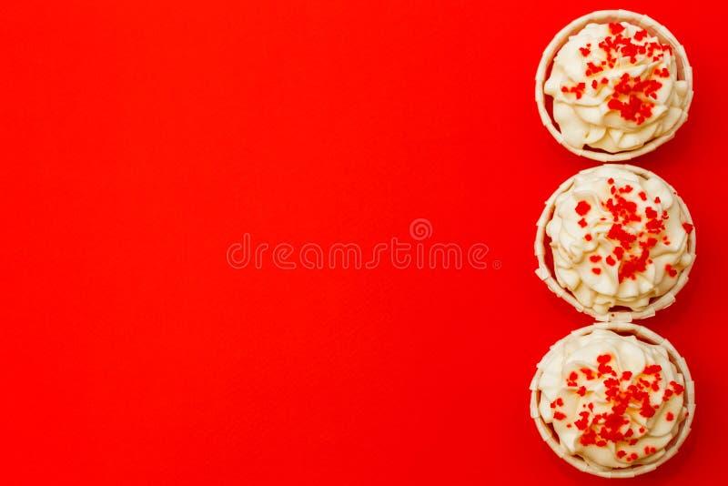 Três queques com creme branco delicado em um fundo vermelho fotos de stock