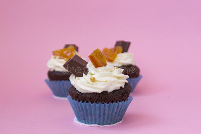 Três queques deliciosos em um fundo cor-de-rosa Bolo branco do creme do ar decorado com chocolate e fruto cristalizado Queques no foto de stock royalty free