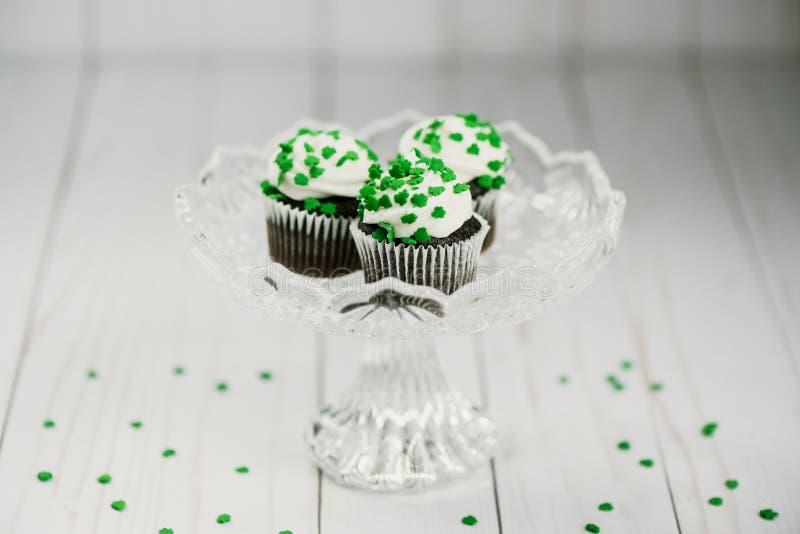 Três queques do chocolate com os doces verdes do trevo em um crysta fotografia de stock