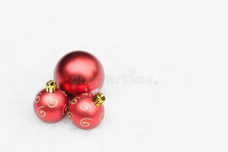 Três quinquilharias vermelhas na neve, ornamento do Natal, espaço da cópia imagens de stock