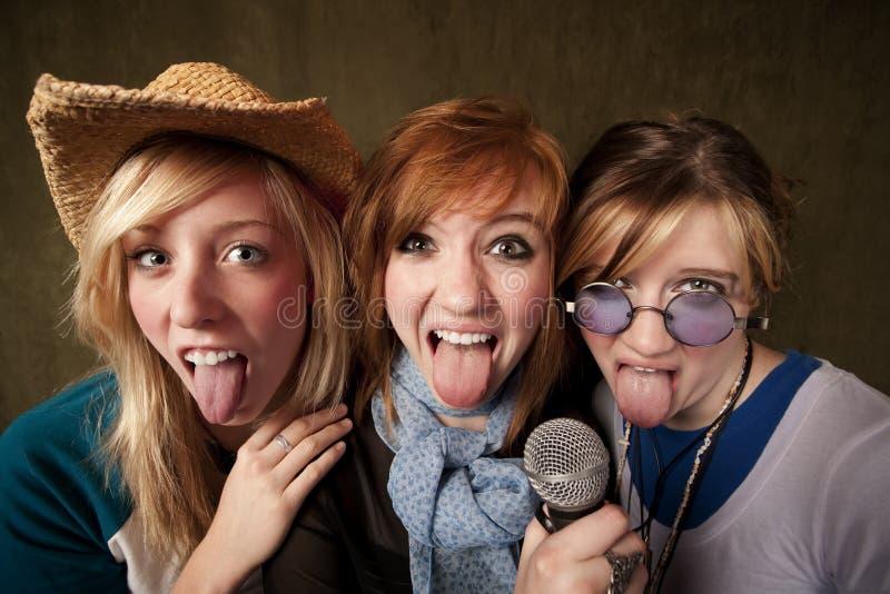 Três raparigas com microfone e lingüetas para fora fotos de stock royalty free