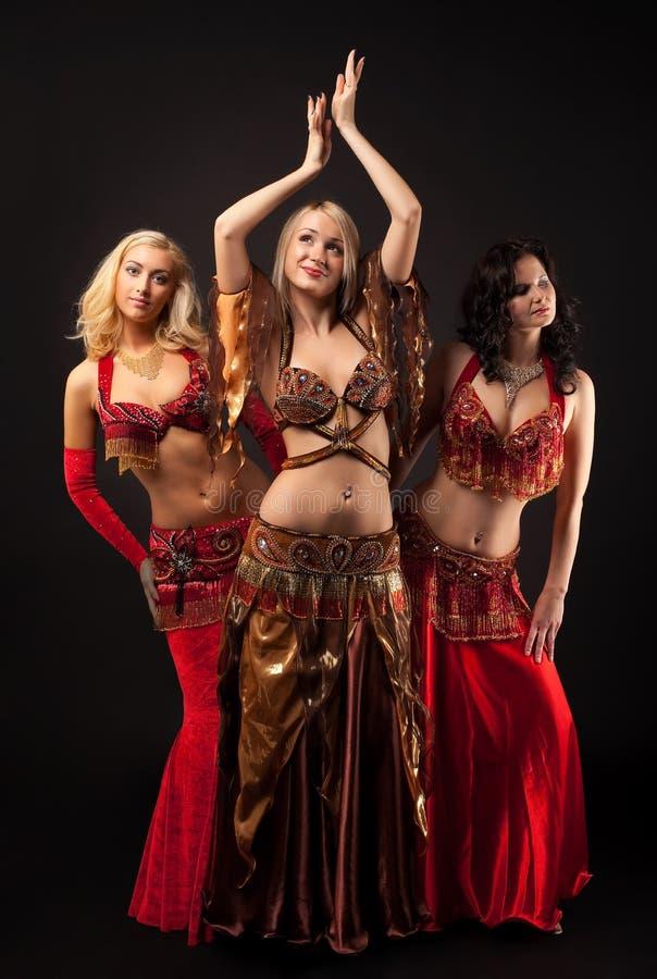 Três raparigas dançam no traje árabe fotografia de stock