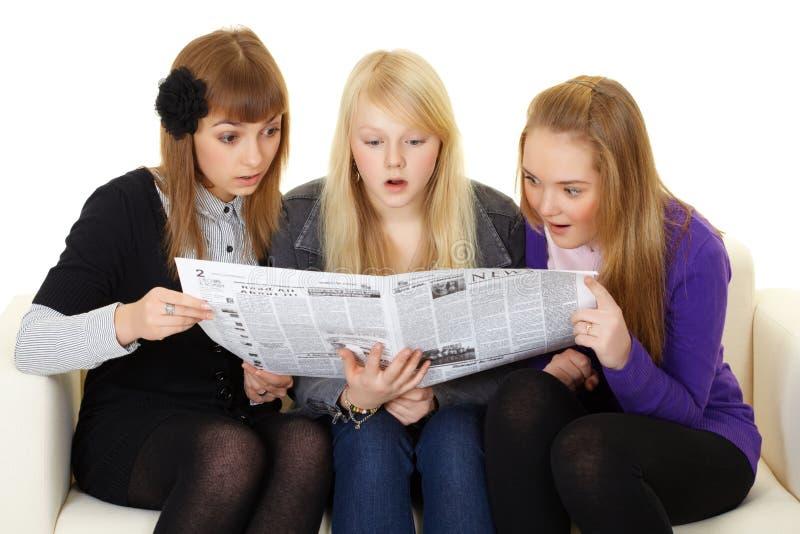 Três raparigas que lêem o jornal fotografia de stock royalty free