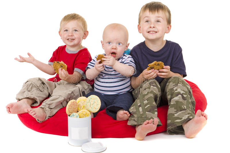 Três rapazes pequenos apreciam comer o bolinho imagem de stock royalty free