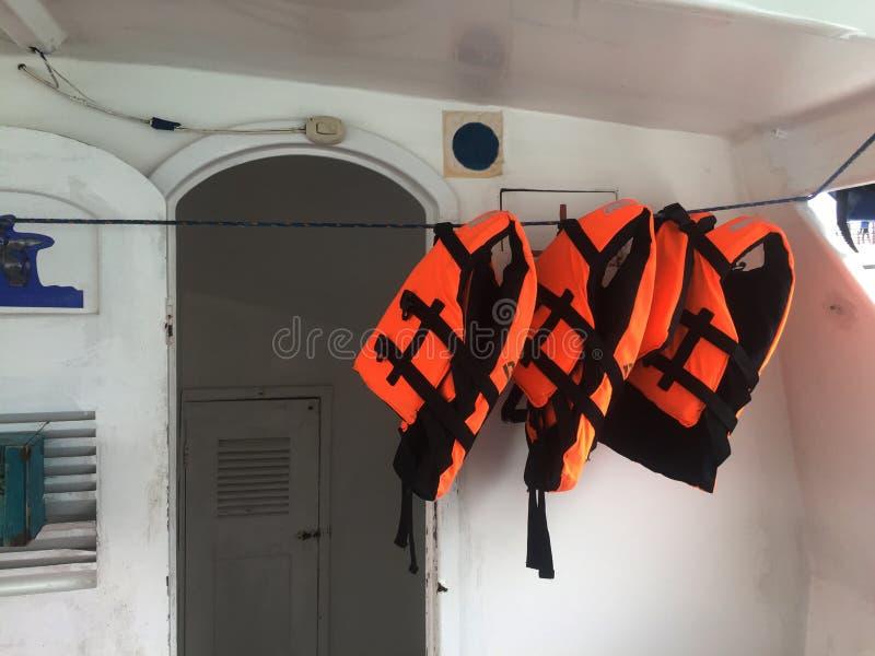 Três revestimentos de vida alaranjados brilhantes que penduram em uma linha em um cabine de um barco imagem de stock