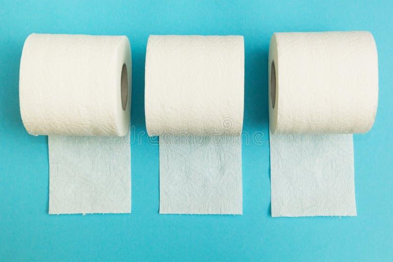 Três rolos de papel higiênico em um fundo azul fotos de stock royalty free