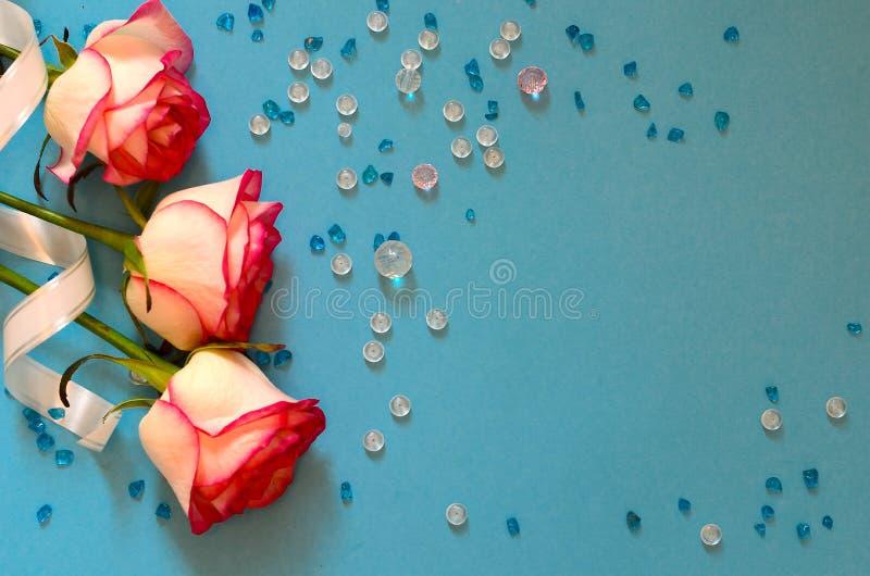 Três rosas cor-de-rosa e grânulos de vidro coloridos em um fundo azul imagem de stock royalty free