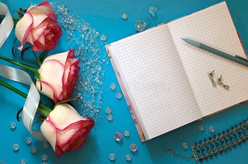 Três rosas cor-de-rosa, um caderno vazio, grânulos, um bracelete em um azul imagem de stock royalty free