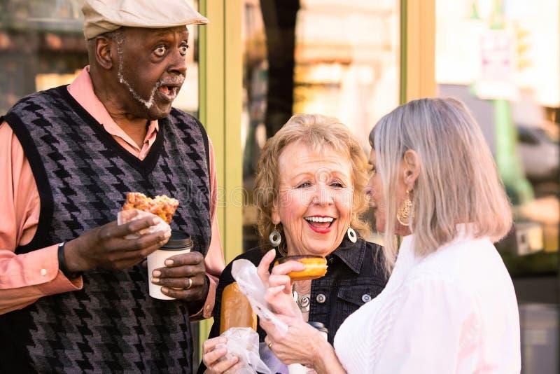 Três sêniores que comem anéis de espuma fora fotografia de stock royalty free