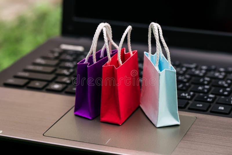 Três sacos de compras de papel coloridos no teclado do portátil Abo das ideias imagens de stock royalty free