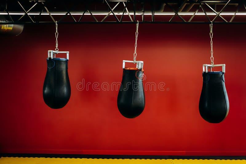 Três sacos de perfuração pretos penduram em uma estrutura do metal contra uma parede vermelha foto de stock