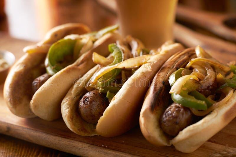 Três salsichas da bratwurst com cebolas e pimentas de sino grelhadas foto de stock royalty free