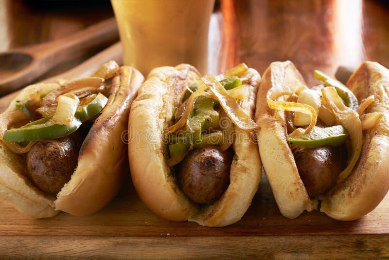 Três salsichas da bratwurst com cebolas e pimentas de sino grelhadas imagens de stock royalty free