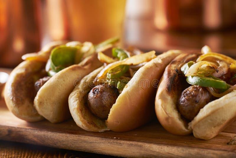 Três salsichas da bratwurst com cebolas e pimentas de sino grelhadas fotografia de stock