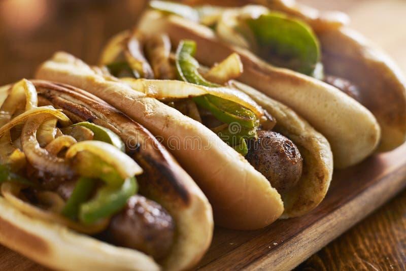 Três salsichas da bratwurst com cebolas e pimentas de sino grelhadas imagens de stock