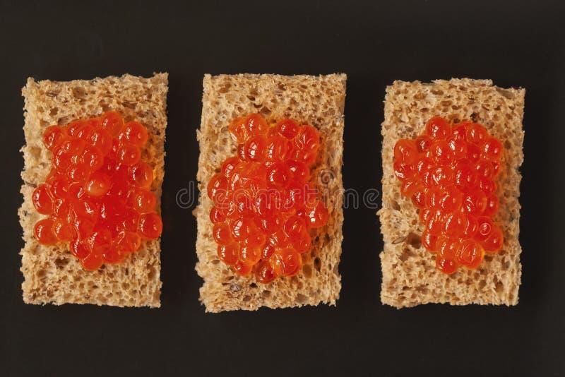 Três sanduíches, canapes com o caviar natural em uma placa escura, vista superior dos salmões vermelhos imagem de stock royalty free