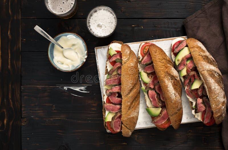 Três sanduíches com a carne grelhada e a cerveja na placa de madeira fotografia de stock