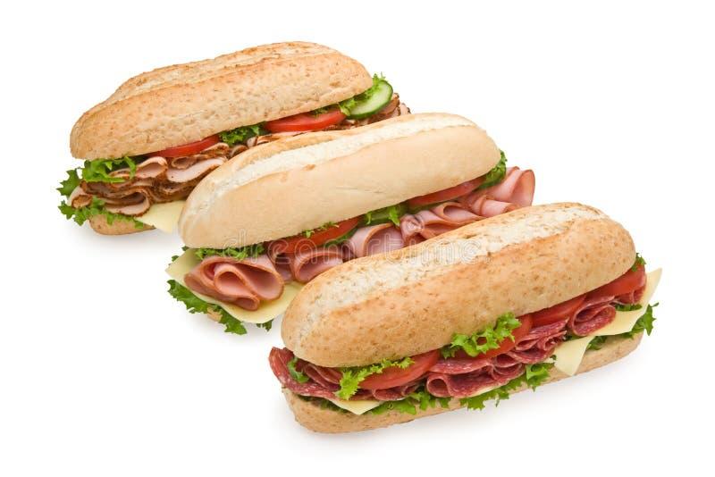 Três sanduíches submarinos deliciosos no branco fotografia de stock
