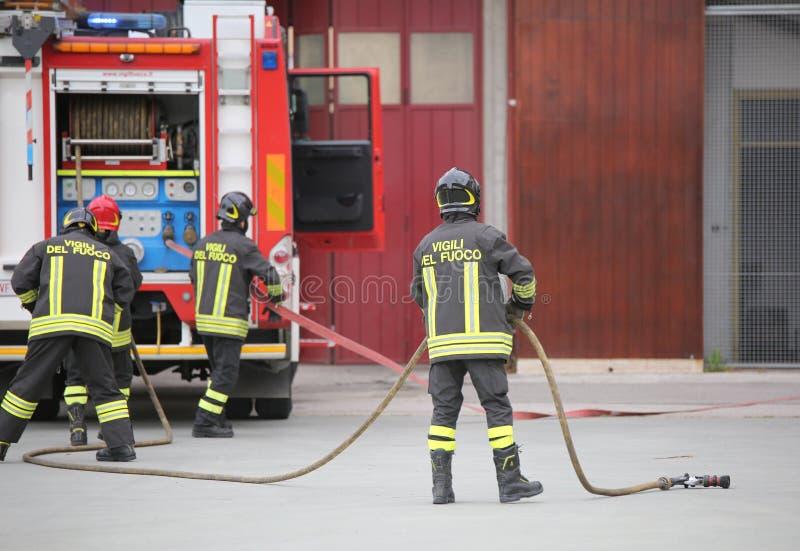 Três sapadores-bombeiros italianos com uniforme e texto Vigili del fuoc foto de stock royalty free