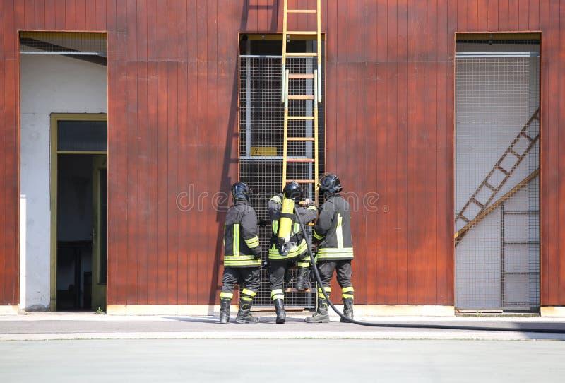 três sapadores-bombeiros no corpo dos bombeiros imagens de stock