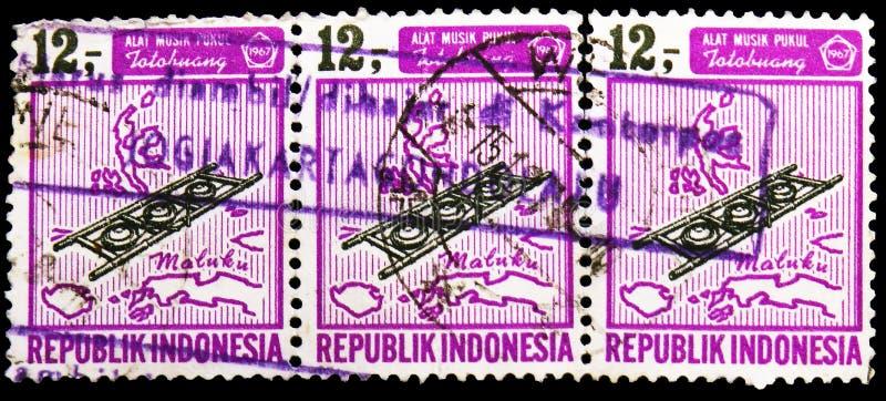 Três selos postais impressos em Indonésia mostram os instrumentos musicais, serie, cerca de 1967 imagem de stock