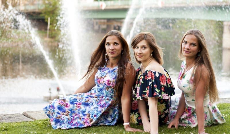 Três senhoras em vestidos do verão no parque fotos de stock royalty free