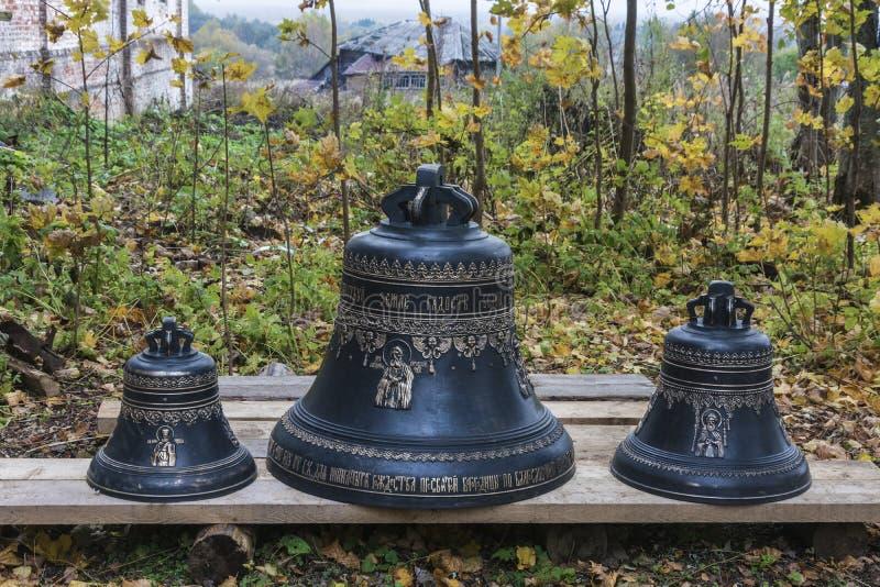 Três sinos pretos ortodoxos com a pintura do ouro, estando em placas de madeira no dia do outono fotos de stock royalty free