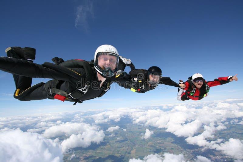 Três skydivers dão forma a uma linha fotos de stock royalty free