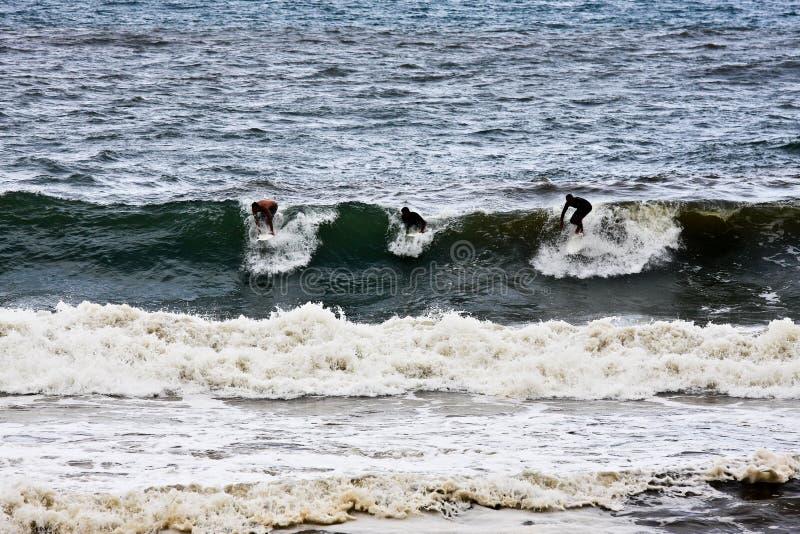 Três surfistas fotografia de stock