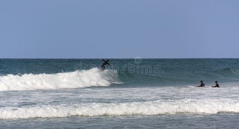 Três surfistas na água durante o treinamento foto de stock