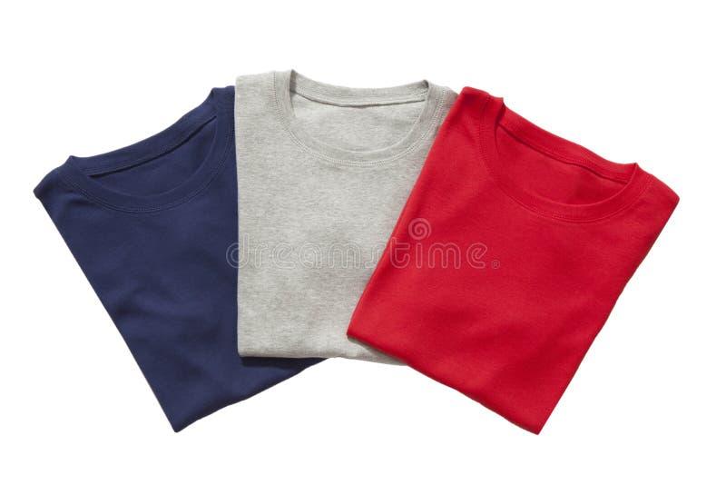 Três t-shirt dobrados isolados imagens de stock