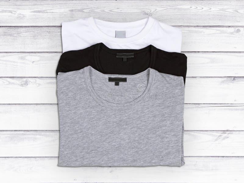 Três t-shirt vazios em um fundo de madeira branco foto de stock royalty free