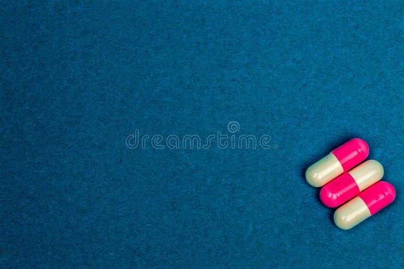 Três tabuletas ovais vermelho-e-brancas em um fundo azul Lugar para escrever fotos de stock