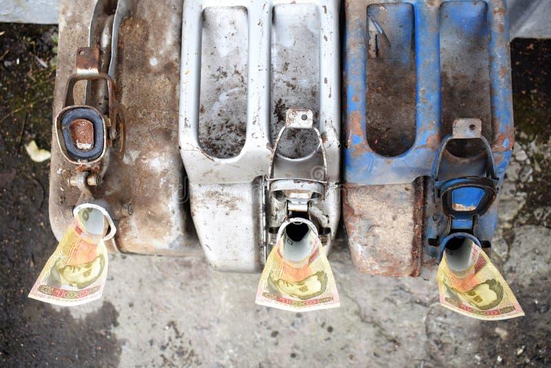 Três tambores do metal e dinheiro ucraniano, o conceito do custo da gasolina, diesel, gás Máquinas de reabastecimento Cédula 100 imagem de stock royalty free
