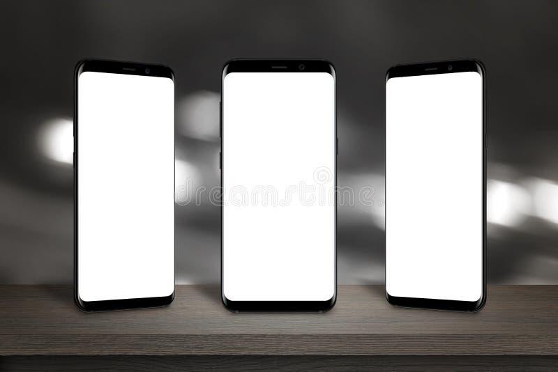 Três telefones celulares com a tela para o modelo na tabela fotografia de stock royalty free
