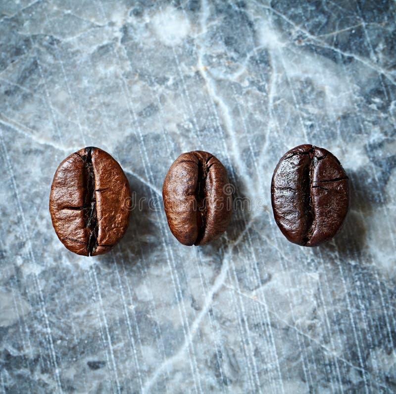 Três tipos de feijões de café em um fundo de mármore imagem de stock