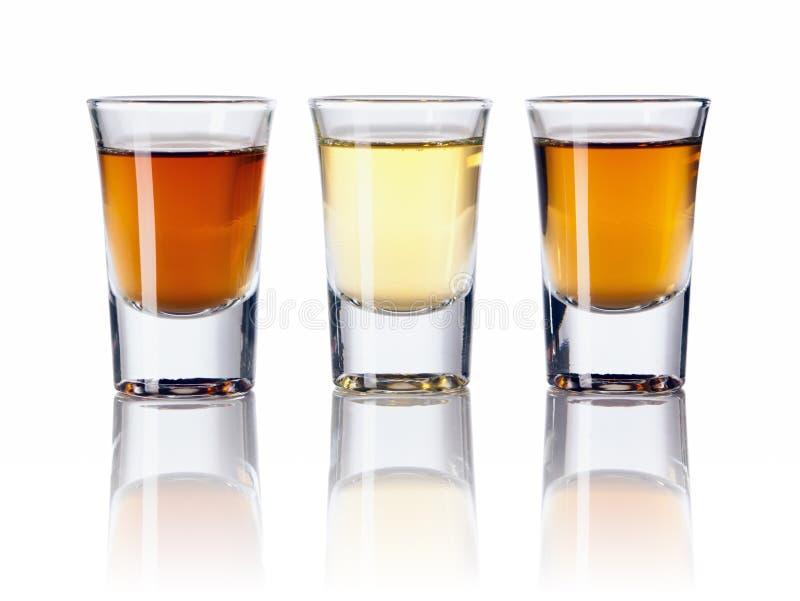 Três tipos de bebidas alcoólicas em vidros de tiro fotografia de stock royalty free