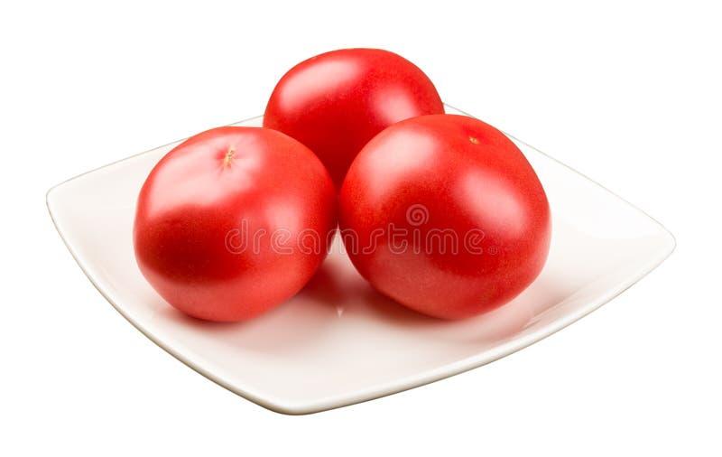 Três tomates em uma placa quadrada fotografia de stock