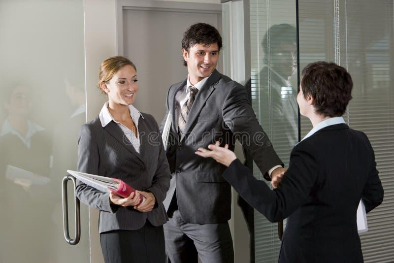 Três trabalhadores de escritório que conversam na porta da sala de reuniões fotografia de stock