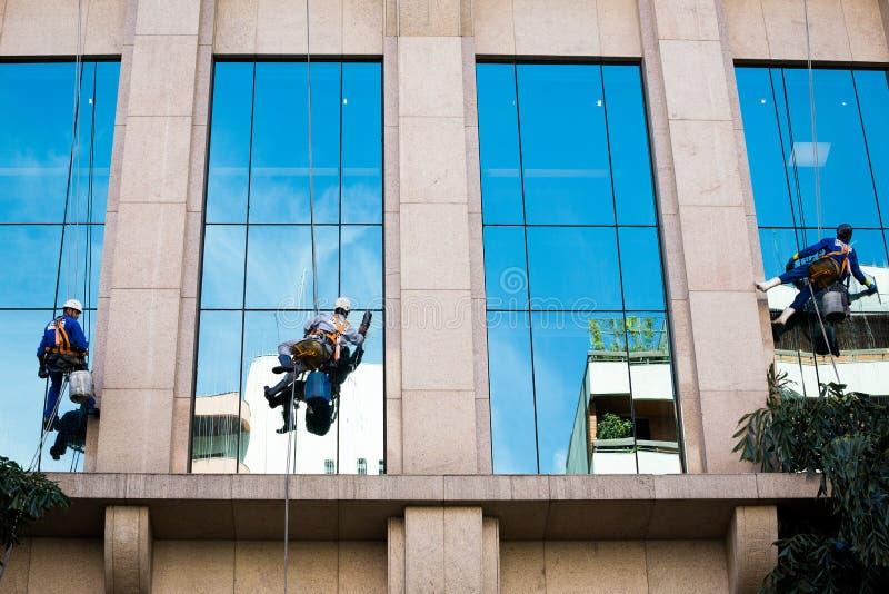 Três trabalhadores que limpam janelas foto de stock