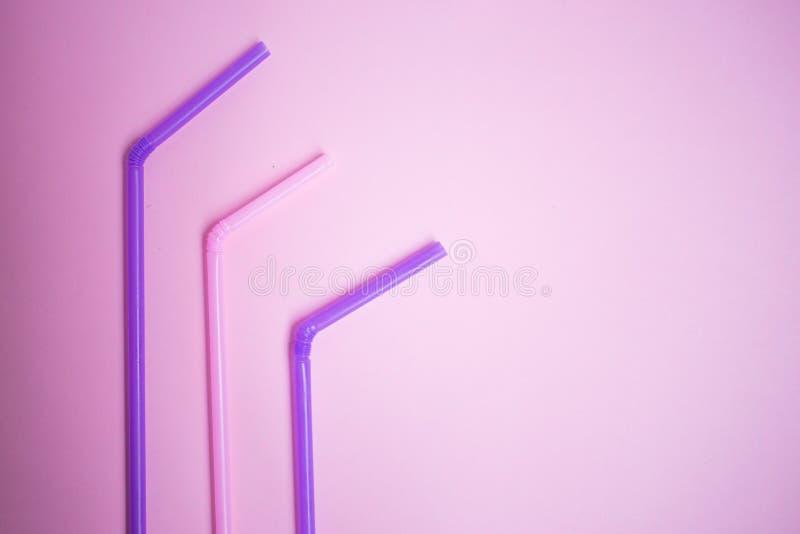 três tubos coloridos do cocktail no fundo cor-de-rosa, partido foto de stock