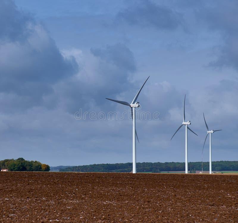 Três turbinas eólicas em um campo do plughed-up imagens de stock