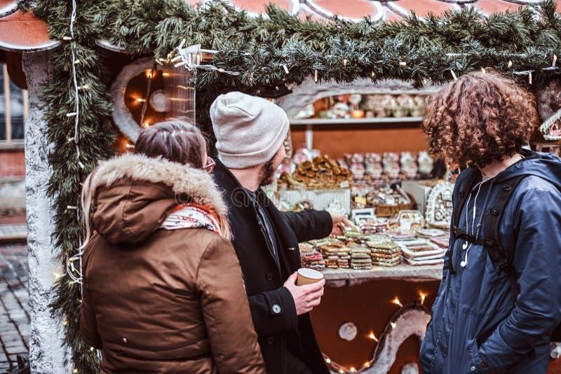 Três turistas consideráveis novos bebem o café em uma casa do café fotos de stock