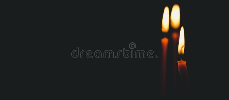 Três velas amarelas da cera que queimam-se com luz da chama iluminam o espaço na igreja, conceito da religião imagem de stock